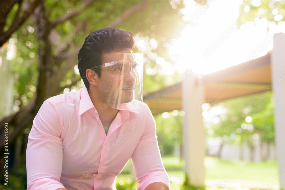 Fototapeta Young handsome Indian businessman with face shield thinking at the park