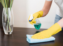 Woman Cleaning The Table With ...
