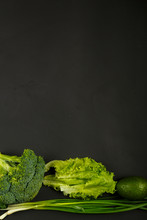 Green Vegetables, Broccoli, Avocado, Onions, Spinach And Salad On The Edge Of A Black Background.
