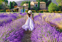 Provence, France. Charming Young Woman In Blooming Lavender Fields At Background Of Beautiful Traditional French Provencal House.  Back View Of Lovely Lady Wearing Waving Boho Chic Purple Dress, Hat.