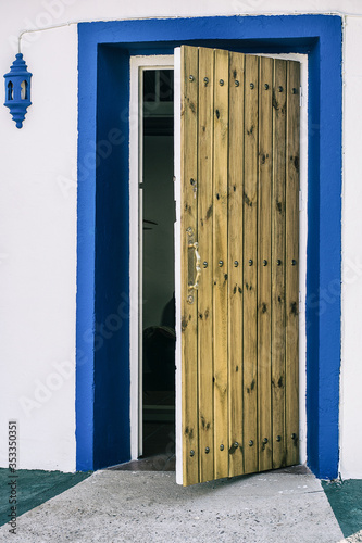 Photo Old wooden door half open, with white wall and blue plinth