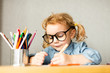 Cute European girl sits at school desk, concept of learning, back to school