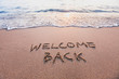 Leinwandbild Motiv welcome back, text on sand beach, tourism after pandemic concept