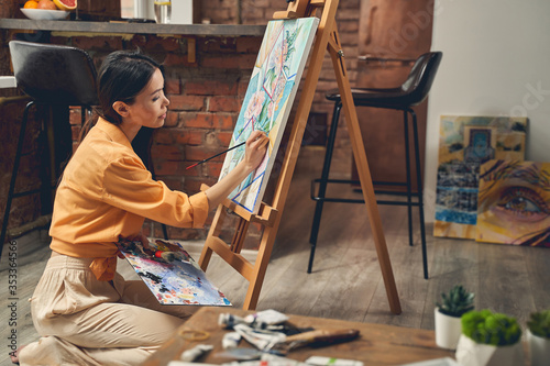 Foto Charming young lady painting picture at home