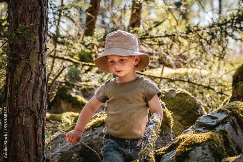 Fototapeta Cute infant boy adventurer playing in the woods in summer in warm evening light