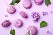 Lilac macarons and lilac flowers on a pastel lilac background. Delicious dessert. Flat lay style. Home cooking