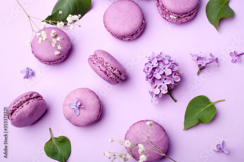 Fototapeta Lilac macarons and lilac flowers on a pastel lilac background. Delicious dessert. Flat lay style. Home cooking obraz