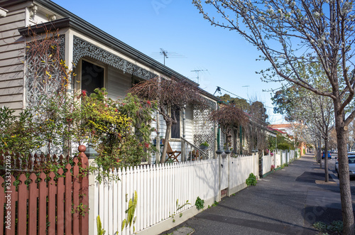 Vászonkép A row of weatherboard houses with  Victorian-era wrought iron lacework and wooden fence in an Australian suburb
