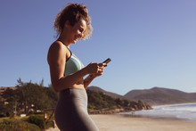 Young Attractive Woman Chatting On Smartphone At The Beach On Sunny Day With Blue Sky.