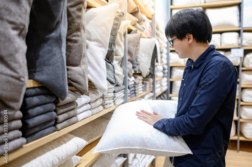 Young Asian man customer choosing throw pillow or sofa (couch) pillow in furniture store Fotobehang