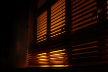Dark, Moody Atmosphere Set By Yellow Light Softly Piercing Through The Blinds. The Shutters Create A Contrast Between Light And Shadow. Concept Of Mafia, Fear, Kidnapping, Sleep, Covid19, Confinement.