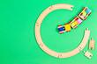 Leinwandbild Motiv Toy train moves on round wooden railways on light green background. Top view