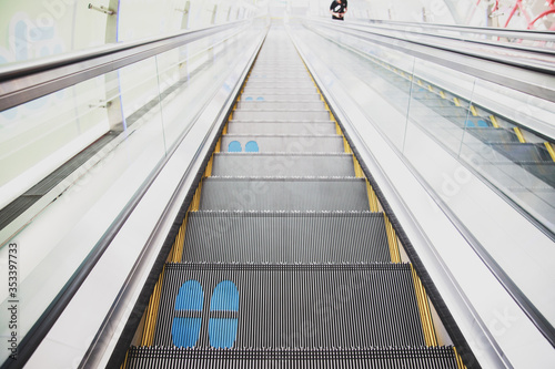 Footprints printed on the escalator for social distancing Wallpaper Mural