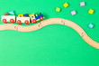 Leinwandbild Motiv Wooden toy train with colorful blocks and wooden railway on light green background