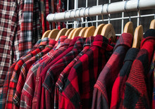 Textured Red Flannel Shirts Hanging On Clothes Rack In Thrift Shop
