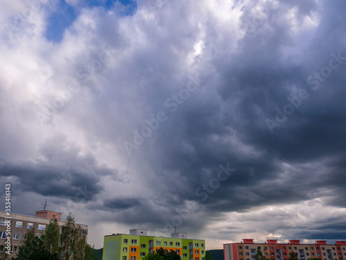 Fotomural Dramatic heavy and dark rain clouds over houses