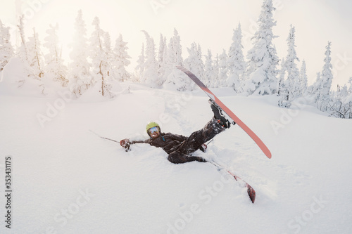 Fotomural Male skier falling down on fresh snow powder between snow-covered trees