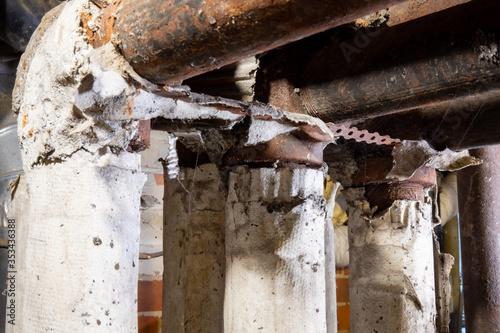 Fotografia dangerous broken asbestos wrap insulation on rusty heating system pipes