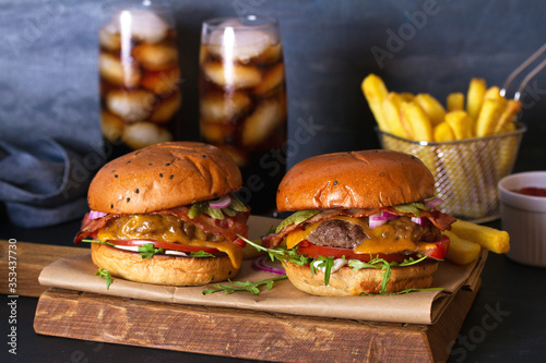 Fototapeta Beef burgers and french fries on serving board. Street food, fast food obraz
