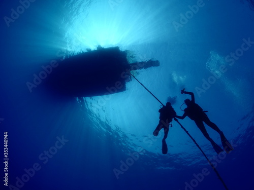 Obraz na płótnie scuba divers ascending descending on the line of boat rope underwater blue decom