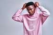 Close up of young african american man in pink streetwear hoodie with hood on head posing isolated on grey background in studio.