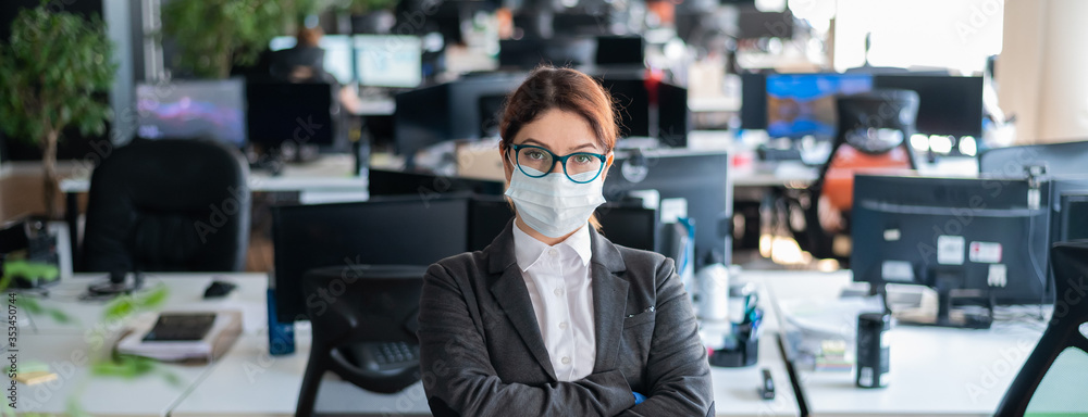 Fototapeta Business woman in office in a protective mask and gloves. Female manager with glasses and a suit works in an epidemic of coronavirus. Caring for the health and safety of staff. Mask mode.