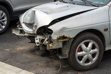 Front Part Of A Grey Passenger Car Damaged In An Accident Or Traffic Accident. Broken-down Car, Insurance Payments. Disposal Of Damaged Cars. Repair Of Machines.