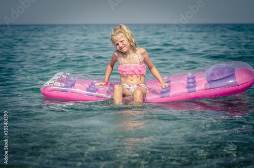 Obraz na plátně cute girl sitting on inflatable pink airbed