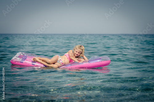 Fotografie, Obraz cute girl lying on inflatable pink airbed