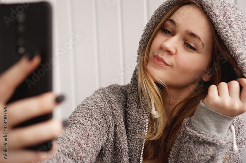 Obraz Picture of young happy emotional pretty lady indoors. Looking camera make selfie - fototapety do salonu