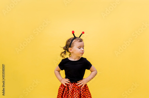 Photo An aggrieved little girl in a ladybug costume on a yellow isolated background with space for text