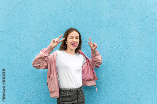 Cuadros en Lienzo Portrait of funny caucasian teen girl in blank white t-shirt and pastel pink bomber jacket against blue city wall solid background