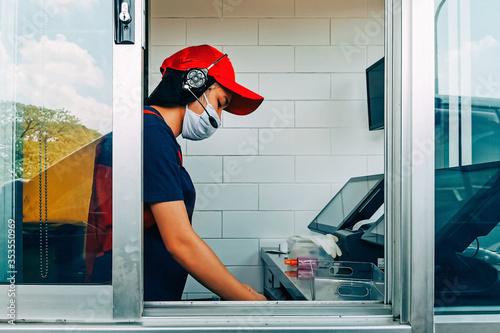 Fototapeta Bangkok, Thailand - May 28, 2020 : fast food cashier in drive thru service wearing hygiene face mask to protect coronavirus pandemic or covid-19 virus outbreak working on counter at the station. obraz