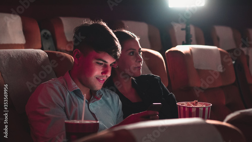 Men playing games on mobile phones he makes his girlfriend annoy and Interfere with watching the movie Wallpaper Mural