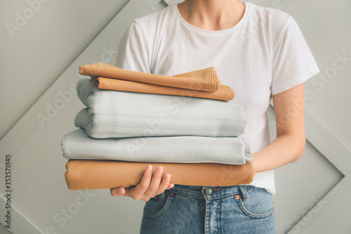 Fototapeta Woman with stack of clean bed sheets on light background obraz