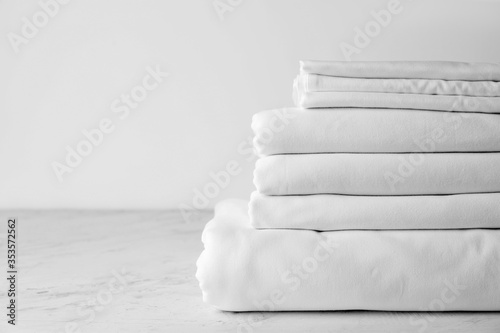 Fototapeta Stack of clean bed sheets on table