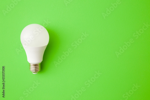Obraz One white led light bulb on bright green table background. Closeup. Energy saving. Empty place for text or logo. Top down view. - fototapety do salonu