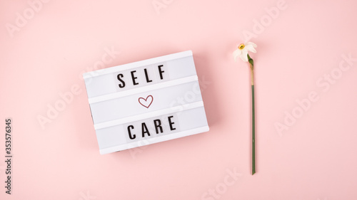 Fotografiet Self-care word on lightbox and flower narcissus on pink background flat lay