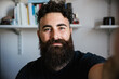 Portrait of friendly blogger smiling bearded hipster man taking a selfie in lockdown from Coronavirus, Covid-19 - Concept of video call teacher job in interview call recording vlog webinar with webcam