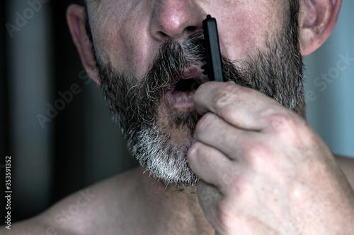 Fotografía close-up of handsome man brushing his beard