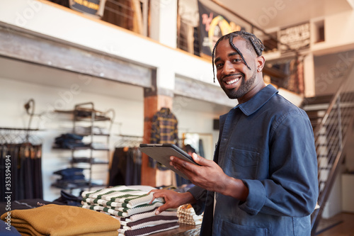 Portrait Of Male Owner Of Fashion Store Using Digital Tablet To Check Stock In C Canvas