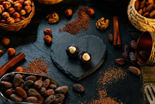Cut Handmade Chocolate Candy With Haselnut On Blackstone Stand In Heart Shape. Chocolate Candies With Cocoa Beans, Nuts, Cocoa Powder Around