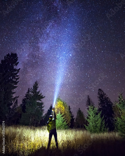 Silhouette of climber standing against the Milky Way with a flashlight in his hands. Location Carpathian, Ukraine, Europe. Astrophotography of milkyway. Dramatic scene. Discover the beauty of earth. #353602174