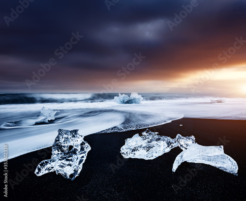 Incredible pieces of the iceberg sparkle on black sand. Location Jokulsarlon lagoon, Diamond beach, Iceland, Europe. #353602338