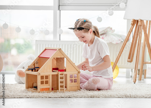 Valokuva Pretty little girl playing with dollhouse