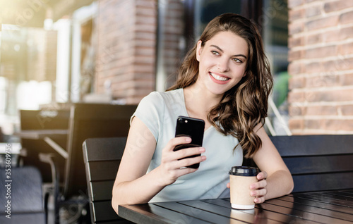 Foto Young beautiful happy woman using smartphone at cafe, Pretty student girl sitting in a coffee shop and looking at mobile phone