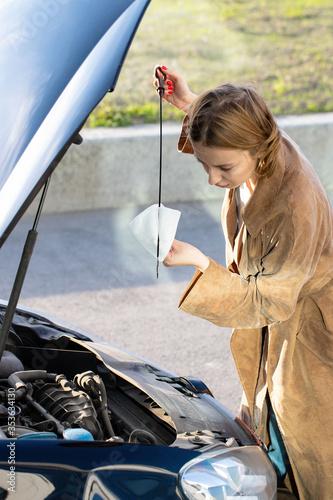 Fotografie, Obraz Confident caucasian woman driver checking oil level in car engine dipstick, cityscape on background