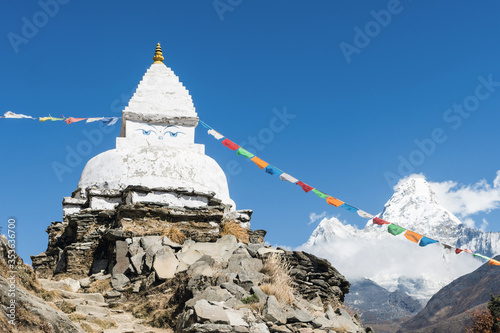 Old white stupa and prayer flags near Pangboche with Ama Dablam in the backgroun Fototapeta