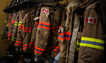 A Rack Of Off-duty Fire Fighters' Bunker Gear Hanging On A Rack Waiting For The Next Call. Brown And Beige With Orange And Yellow Flourescent Stripes And  Showing A Canadian Flag.