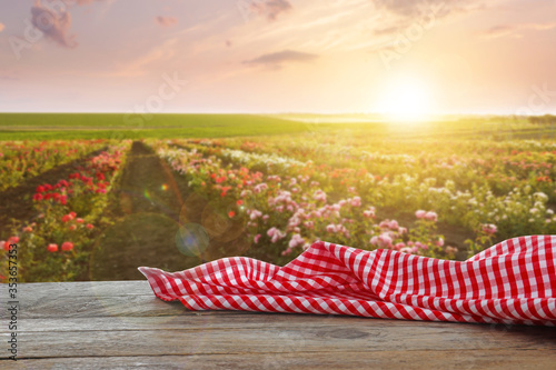 Fotografia Picnic wooden table with checkered red napkin and beautiful roses on background